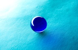 Blue glass ball on blue paper. Magic ball of a witch and fortune teller.
