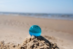 Blue glass ball on sand near the sea. Abstract conceptual photo.