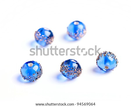 Blue glass beads closeup on white background