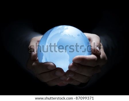 Blue glass earth in human hands