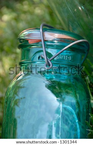 Blue glass jar with a wire holding the lid and rubber ring onto it, used for canning fruits and vegetables, sitting in the grass.
