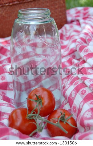 Blue glass jar with a wire holding the lid and rubber ring onto it, used for canning fruits and vegetables, sitting on a vintage table cloth.  Three tomatoes on the vine are sitting near the jar.
