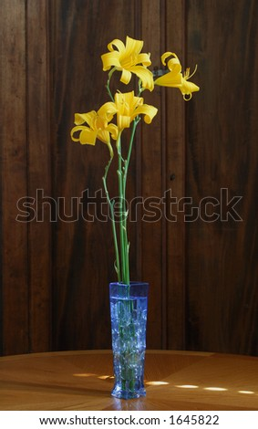 Blue glass vase with glass stones and tall daylilies on oak table.