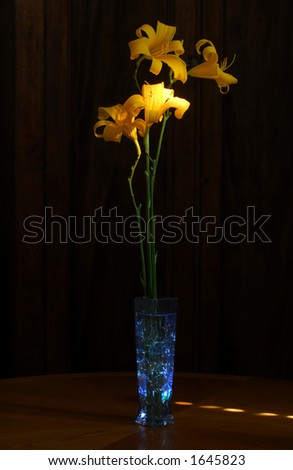 Blue glass vase with glass stones and tall daylilies on oak table, lit with light painting.