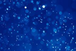 Blue glitter vintage lights background. Blue bokeh on black background.