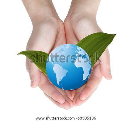 Blue globe over green leaves in hands - stock photo