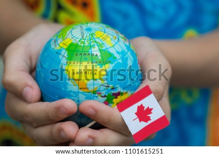Blue globe with territories of the countries of the world and the Canadian flag, territory Canada. Defend Canada from Coronavirus Pardemic