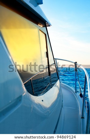 blue golden sunrise sailing on boat side with Mediterranean coastline in horizon