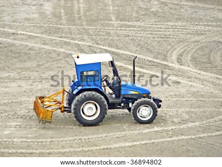 blue grader tractor waiting to clean the beach sand