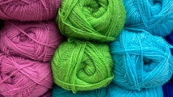 Blue, green and pink of wool yarn. Multicolored skeins of wool close-up