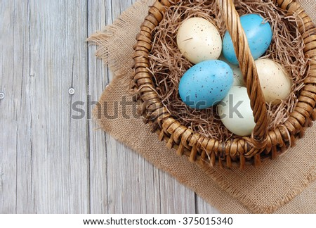 Blue, green and yellow speckled eggs in a basket with brown straw sitting on burlap on a rustic wooden background. Flat lay perspective with copy space on left side. Horizontal composition. #375015340
