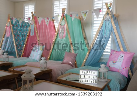 Blue, green, pink and lama teepee's all set up for a sleepover birthday party.  There is also fairy lights, bunting and face masks .  Stock photo ©