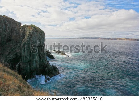 blue green waves crash against a cliffside on the east coast of canada in newfoundland #685335610