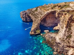 Blue Grotto in Malta. Pleasure boat with tourists runs. Natural arch window in the rock. Aerial top view
