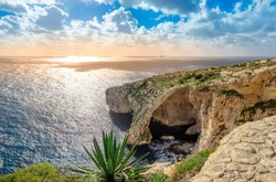 Blue Grotto, Malta. Natural stone arch and sea caves and agave plant in foreground. Phantastic sea view on Malta island.