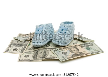 Blue hand made baby booties on some American money isolated on white, Cost of raising a child