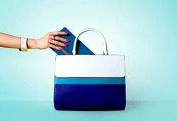 Blue handbag. Taking out the wallet from the purse bag. Isolated on aqua blue background.