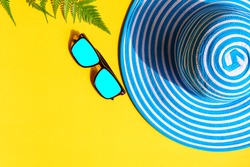 Blue hat and sunglasses on colorful paper with travel and fashion style