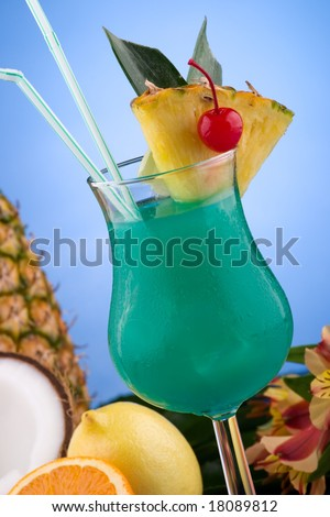 Blue Hawaiian cocktail surrounded by tropical fruits. Rum, pineapple juice, coconut milk and blue curacao garnished with slice of pineapple and maraschino cherry. Most popular cocktails series.