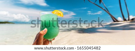 Blue Hawaiian drink cocktail banner on beach vacation background. Woman hand holding beverage. Stock foto ©