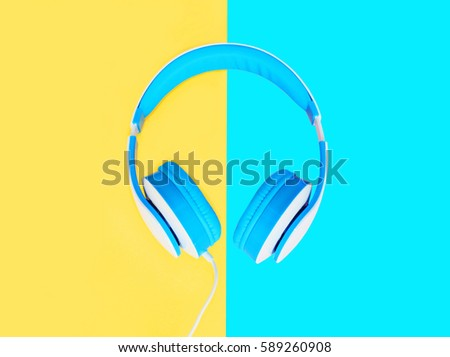 Blue headphones over colorful yellow blue background top view