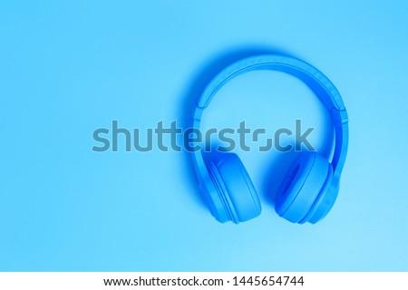 blue headphones, Top view of headphones on blue background. Minimalist photo of earphones with copy space. White dj headphones, Top view blue headphones on blue background