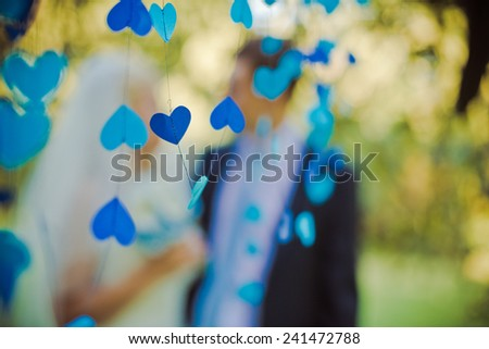 Blue heart in the foreground. High key blurred image of the couple. Unrecognizable faces, bleached effect.