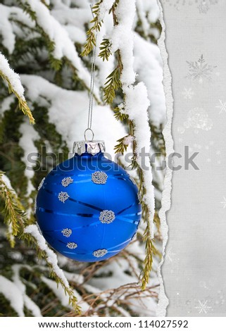 blue holiday ornament on snow covered pine torn edge