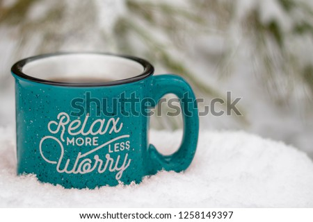 Blue hot mug steam rising relax more worry less on front surrounded by snowy scene & icy pine branches winter background, holiday stress keep calm relax more worry less concept, text copy space