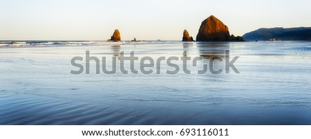Blue hour merges with golden hour in this simplic scene of Cannon Beach, Oregon, two iconic intertidal rocks, Needles and Haystack.  #693116011