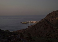 Blue hour night view of Puerto de las Nieves, traditional fishing village port lights with cliffs and rocks and winding road in the north west of Gran Canaria, Canary Islands, Spain.