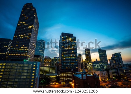 Blue Hour Sunset in Denver , Colorado , USA at Dusk in Downtown City glowing Nightscape Skyline of the Mile High City Skyscrapers and office buildings rising up into the night sky