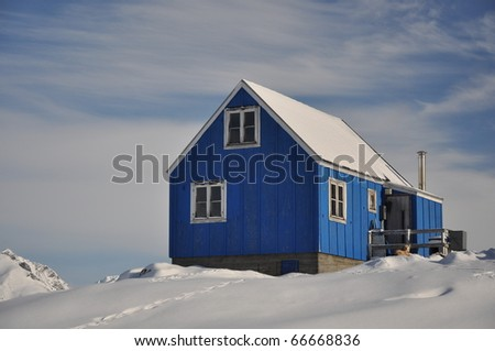 Blue house covered by snow in the Kulusuk village, east Greenland