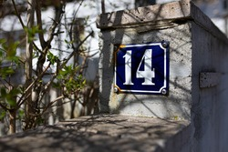 blue house number sign with a rusty corner on a concrete wall with some bushes next to it