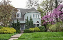 Blue House with Large Round Turret and Spring Foliage