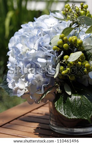 Blue hydrangea blossom and green berries floral arrangement in vase.