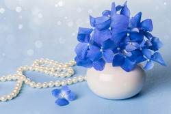 Blue hydrangea in a white vase and a pearl necklace on a light blue background.