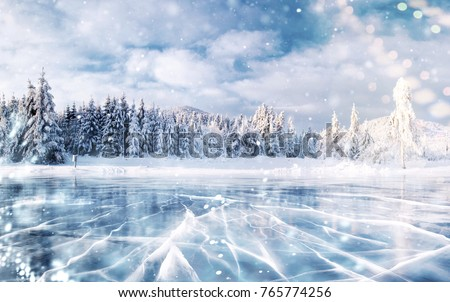 Blue ice and cracks on the surface of the ice. Frozen lake in winter mountains. It is snowing. The hills of pines. Winter. Carpathian Ukraine Europe. #765774256