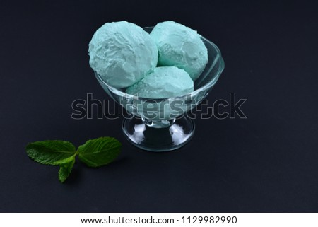 Blue ice cream in cup with mint on black background. #1129982990