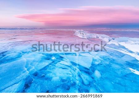 Blue ice of Baikal lake under pink sunset sky #266991869