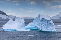 Blue iceberg in the Errera Channel of Antarctica with a backdrop of typical frozen and snow covered Antarctic scenery