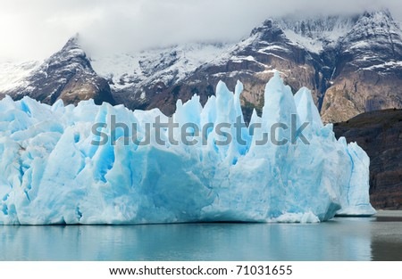 Blue icebergs and snowy mountains at Grey Glacier in Torres del Paine National Park, Patagonia, Chile