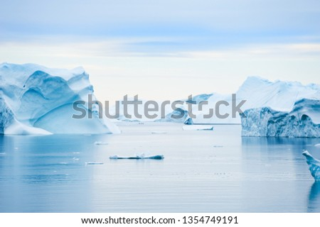 Blue icebergs in Atlantic ocean at sunset. Saqqaq village, west coast of Greenland #1354749191