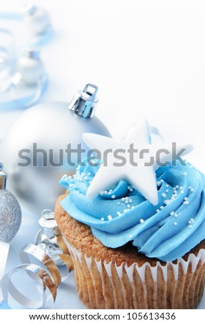 Blue icing frosted cup cake with silver christmas ornaments and decorations, plenty of copy space