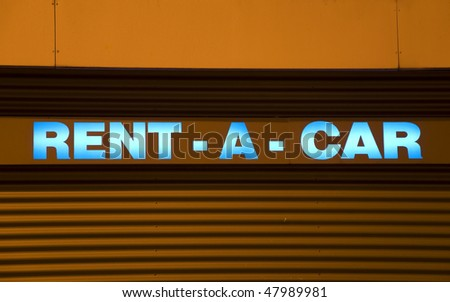 blue illuminated rental car sign with orange background