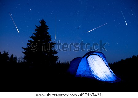 Blue illuminated tent with travelers in the mountain. Background of a pine tree silhouette and the starry summer night sky. Meteor shower. Falling stars.
