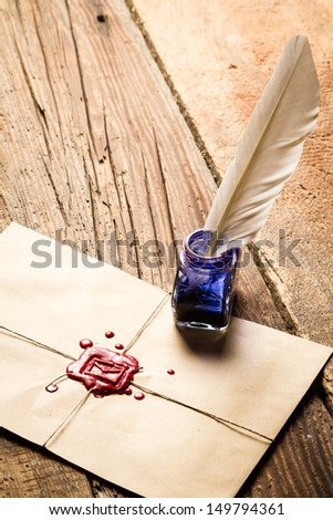 Blue ink inkwell with feather on envelope with red sealant