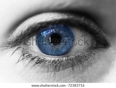Blue iris eye over black and white. Closeup