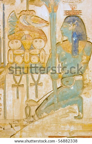 Blue Isis goddess with food tray Goddess Isis carrying a tray of food including ducks and bread.  Wall of the Temple of Ramses II at Abydos, Egypt.