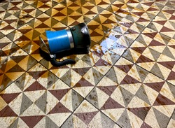 Blue italian coffee maker machine on kitchen tiled floor with spilt coffee all over